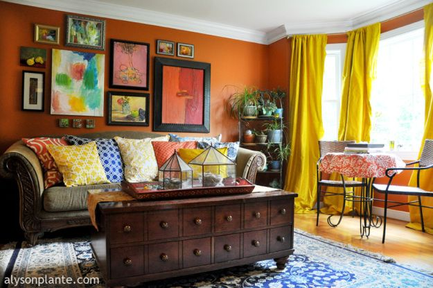 colorful vintage living room apartment wall art | artsy living room // yellow silk drapes // orange walls ...