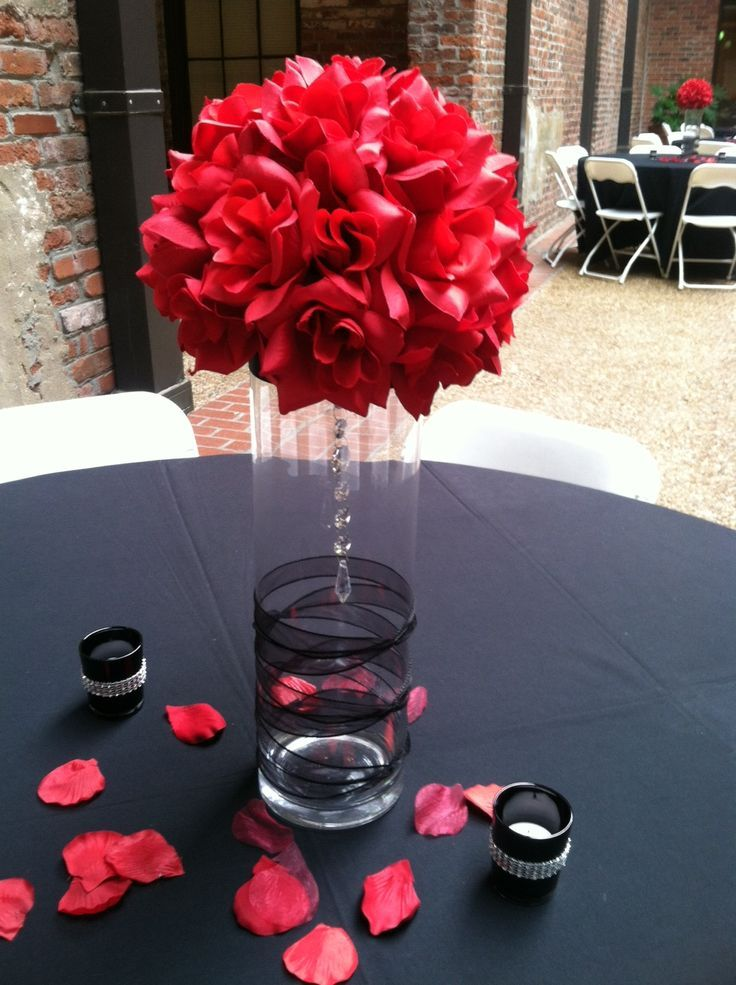 Stunning idea for a black and red themed wedding centerpiece with a glass vase decorated in black lace, crystals and red flowers. Black tablecloth with loose red petals. More Great Looks Like This