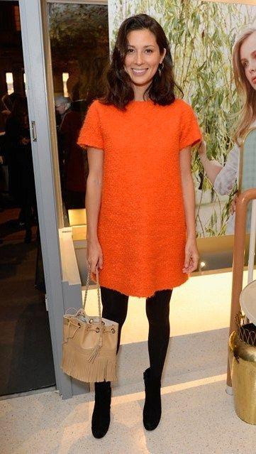 Jasmine Hemsley in a bright orange shift dress and black tights
