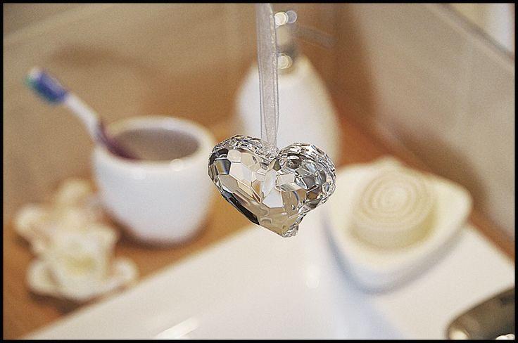 Biały zestaw łazienkowy, a nad nim kryształowe serduszko zdobi nie tylko lustro ale i całe pomieszczenie.