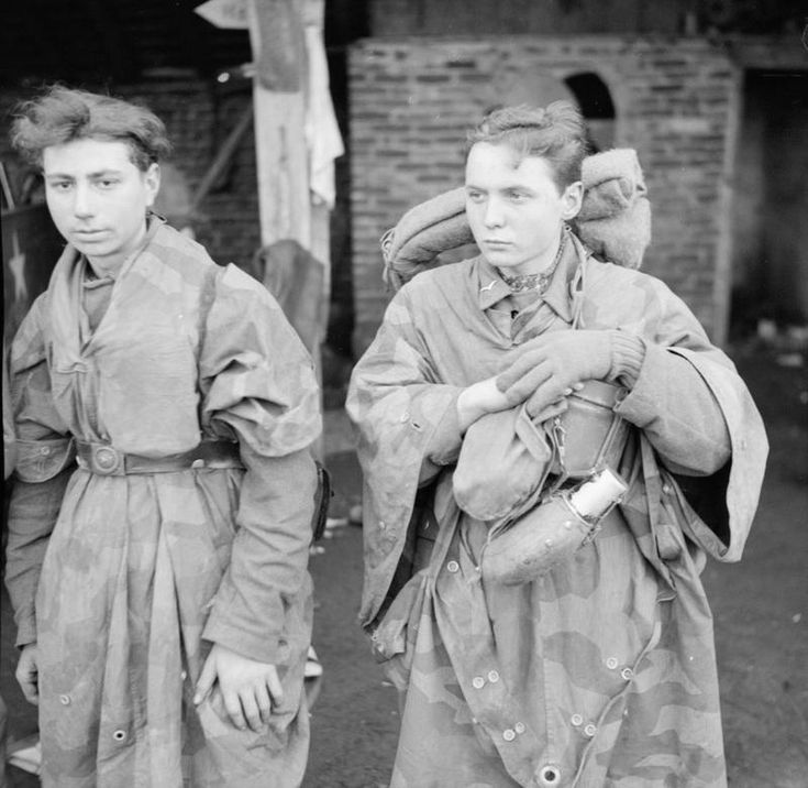 Two dishevelled young German POWs captured in the Dingden area of Hamminkeln, Germany. An estimated 20,000 German troops were captured during the first five days of the British assault following the crossing of the Rhine. *Note the camouflage smocks worn by both youngsters. Ironically, such kit became widely available among German soldiers in the closing months of the war.