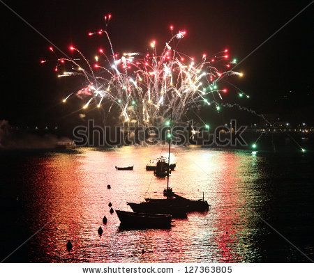 LEVANTO, ITALY - JULY 25: Fireworks explode on the bay water during San Giacomo celebrations July 25, 2012 in Levanto, Italy. - stock photo