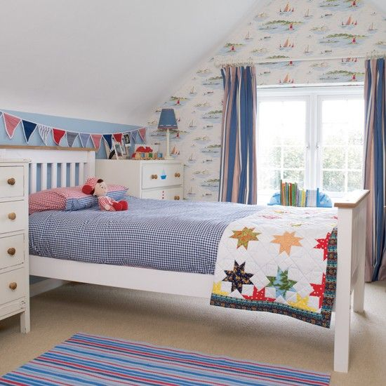 Colourful boy's bedroom ~ This colourful boy's room has been inspired by the sailing boat wallpaper, with red and blue accessories tying in with the design. White painted furniture adds a classic touch and bunting injects more colour and fun into the room.