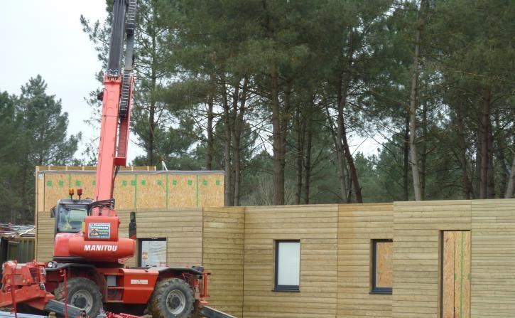Mars 2014 : pose des complexes de murs préfabriqués avec les fenêtres et le bardage bois.