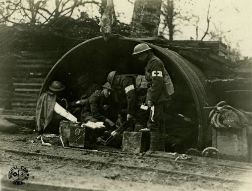 American medics of the 79th Infantry Division treating wounded comrades at an aid station in Bois de Consenvoye, France, November 9, 1918.