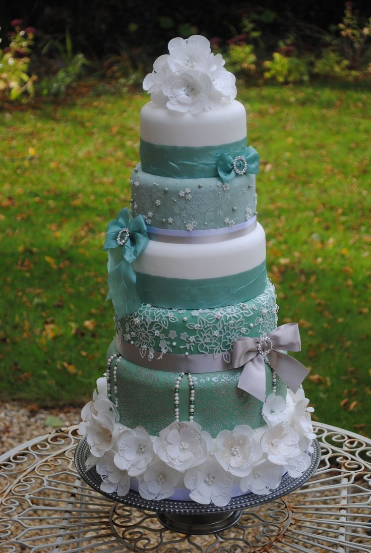 Teal and white vintage floral rose cake with pearls - This six tiered cake incorporates all of Cake Crafting's specialist cake decorating tools. Two tiers have been stencilled using our Rose Flourish stencils and the rest has been embellished with wafer paper flowers using the Lavish Blooms Poppy and Adele Flower cake dies. We have also used the Bow Maker to add extra detail between the tiers. www.cakecrafting.co.uk