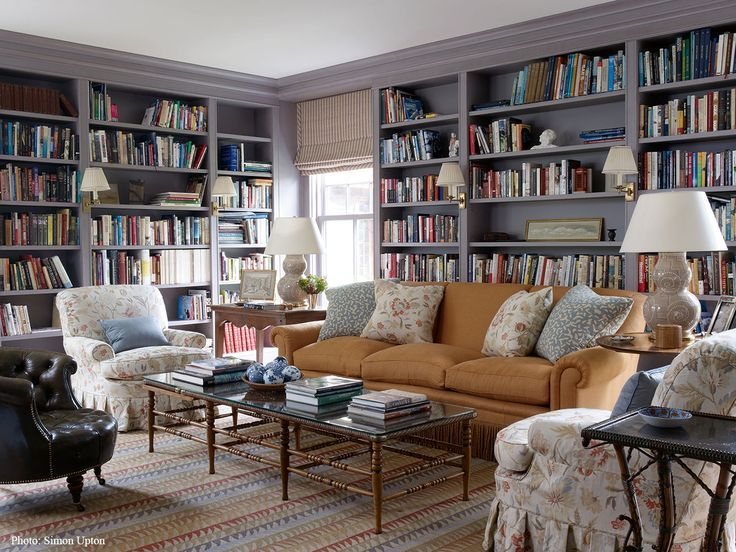 Home library with painted built-in bookshelves, soft goldenrod sofa, comfy chairs, lamps, and a coffee table.