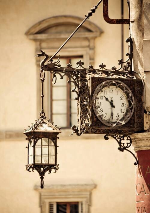 Artistry of a clock and lantern in Italy.