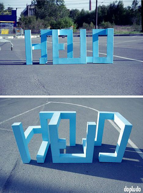"""In this clever work by Dopludo Collective, three-dimensional shapes that stand up on their own in a parking lot reveal themselves to be a word when viewed from a certain angle."""