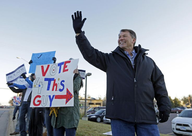 Republican U.S. Senate candidate Mike Rounds campaigns with supporters during the morning commute in Sioux Falls, S.D., Tuesday, Nov. 4, 2014. Rounds, former South Dakota governor, faces Democrat Rick Weiland and Independents Gordon Howie and Larry Pressler. (AP Photo/Michael Conroy)