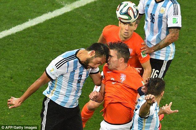 Bruised: Argentina defender Ezequiel Garay (left) was aggressive and resolute against Van Persie (center).