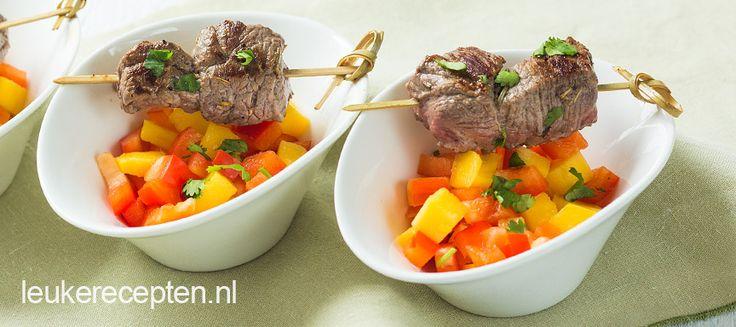 Gezond hapje van gebakken bief aan een spiesje met een salsa van mango en paprika