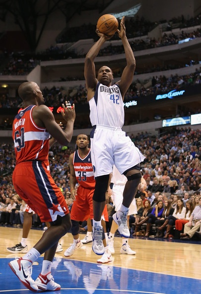 Elton Brand #42 of the Dallas Mavericks takes a shot against Emeka Okafor #50 of the Washington Wizards at American Airlines Center on November 14, 2012 in Dallas, Texas.