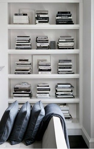 Neat stacks of books on white shelving