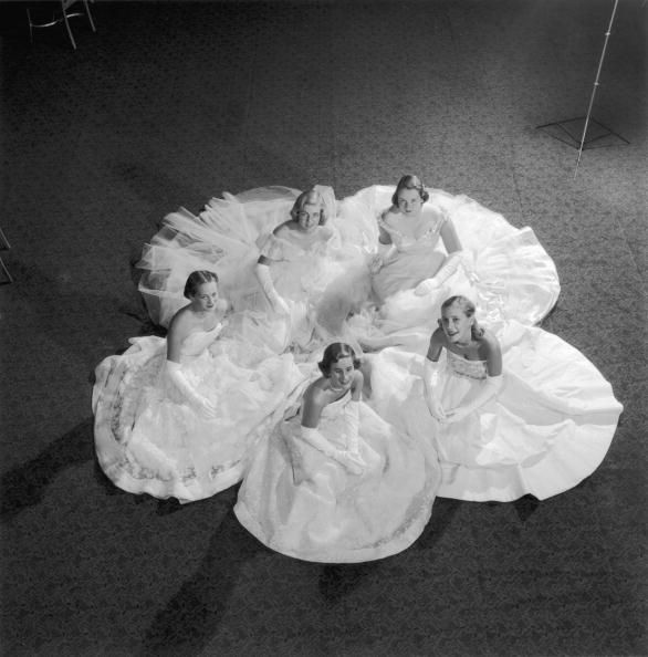 Title: Five Debutantes  Caption: November 1951: Five members of the Debutante Cotillion rehearse for the Christmas Ball at the Waldorf Astoria Hotel in New York. Clockwise from the bottom: Ann Firestone, Venetia Arlen, Mary Audrey Weicker, Sarane Hickox and Peggy Hitchcock.   Artist: Slim Aarons  Date: 1951