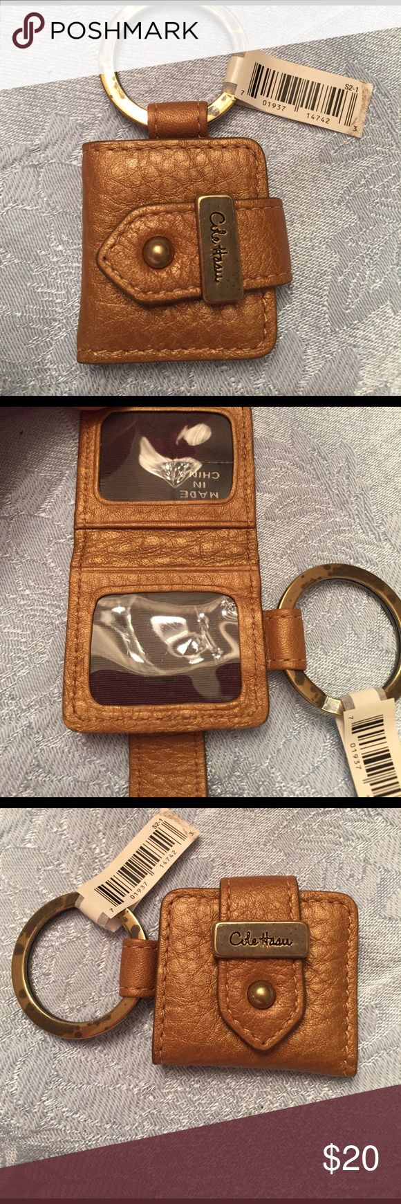 SALE! COLE HAAN photo key chain!! Authentic. COLE HAAN leather, photo, key fob, in the color bronze. Brand new with tags. Guaranteed 100% Authentic. I took it out of the original package for photo purposes. This cute key chain opens up and can hold two pictures. There is some discoloration on the metal key loop; view posted photos. This is perfect to carry your keys and keep precious photos of your loved ones close to you. Cole Haan Accessories Key & Card Holders