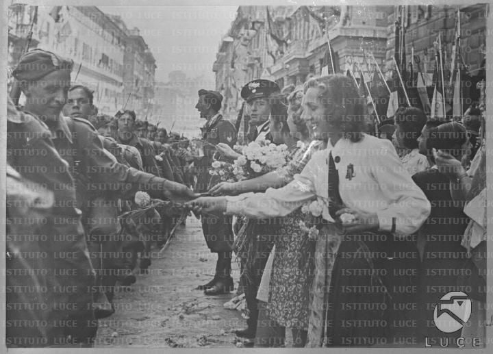 Ragazze donano dei fiori ai volontari della G.I.L. che sfilano: in primo piano una Giovane Italiana offre un fiore a un milite  RG/RG106/RG00004193.JPG