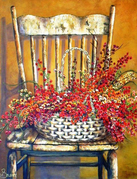 Stella Bruwer wicker basket of red and orange flowers on shabby  cream chair with scalloped back