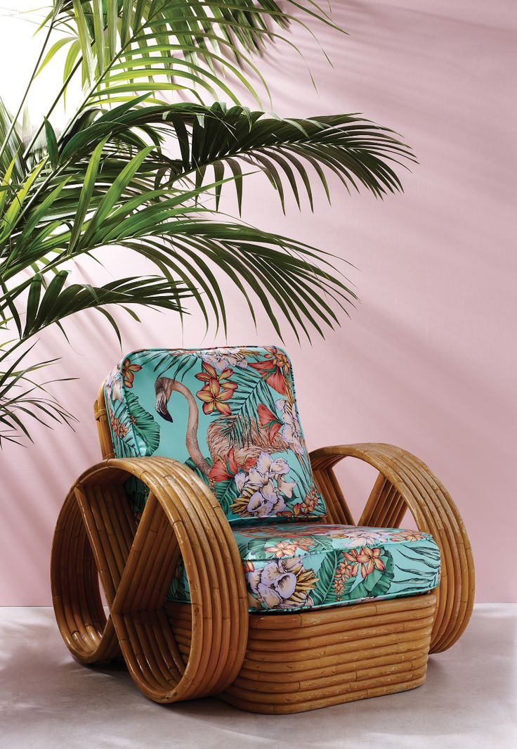 Matthew Williamson in collaboration with Osborne & Little. The Flamingo Club fabric from the 2015 Cubana collection. A colourful depiction of flamingos peering though exotic flora, printed on pure cotton. A modern wooden arm chair upholstered in The Flamingo Club print sits against a pale pink wall.