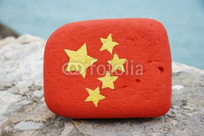 China flag on a stone over a rock front of the sea