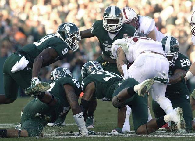 MSU defenders gang up on Stanford running back Tyler Gaffney and stop him at the line of scrimmage, 100th Rose Bowl Game, 01/01/2014