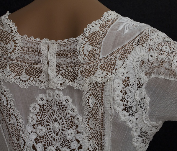 [Embroidered tea dress embellished with Irish crochet, c.1905. Without the original boned underpinnings, the dress is comfortable and easy to wear. The soft feminine style and delicious detail will appeal to your inner princess. The design uses a textured assortment of machine lace with accents of hand-embroidered floral appliqués and handmade Irish crochet flowers (the unifying element of the design). I love the smocked shirring on the sides of the lower skirt.]