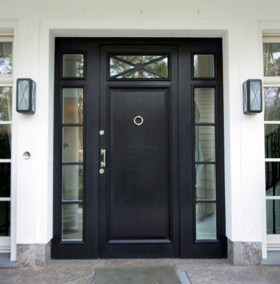 Rezydencjonalne drzwi zewnętrzne. Drzwi pojedyncze, choć optycznie powiększone o boczne skrzydełka oraz górne naświetle, które wspaniale oświetlają wnętrze rezydencji. Drzwi dwukolorowe, od zewnątrz czarne, wewnątrz białe. Single, oak exterior doors, white inside, black outside, wing with glass