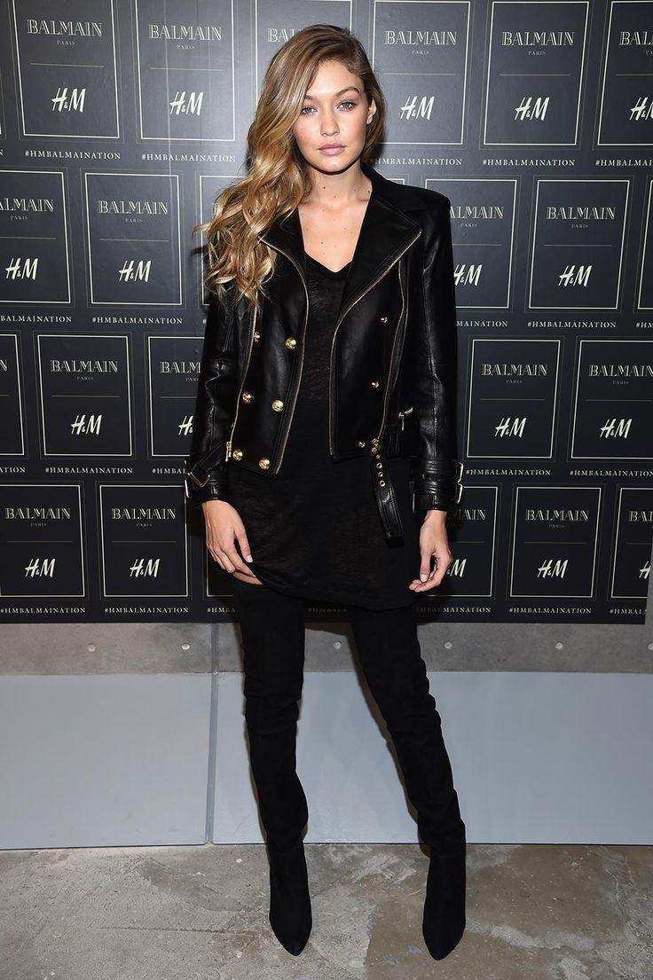 Gigi Hadid musa de all black, jaqueta de couro com botões, fivela e zíper dourados e bota de cano alto. Toda de preto com louvor!