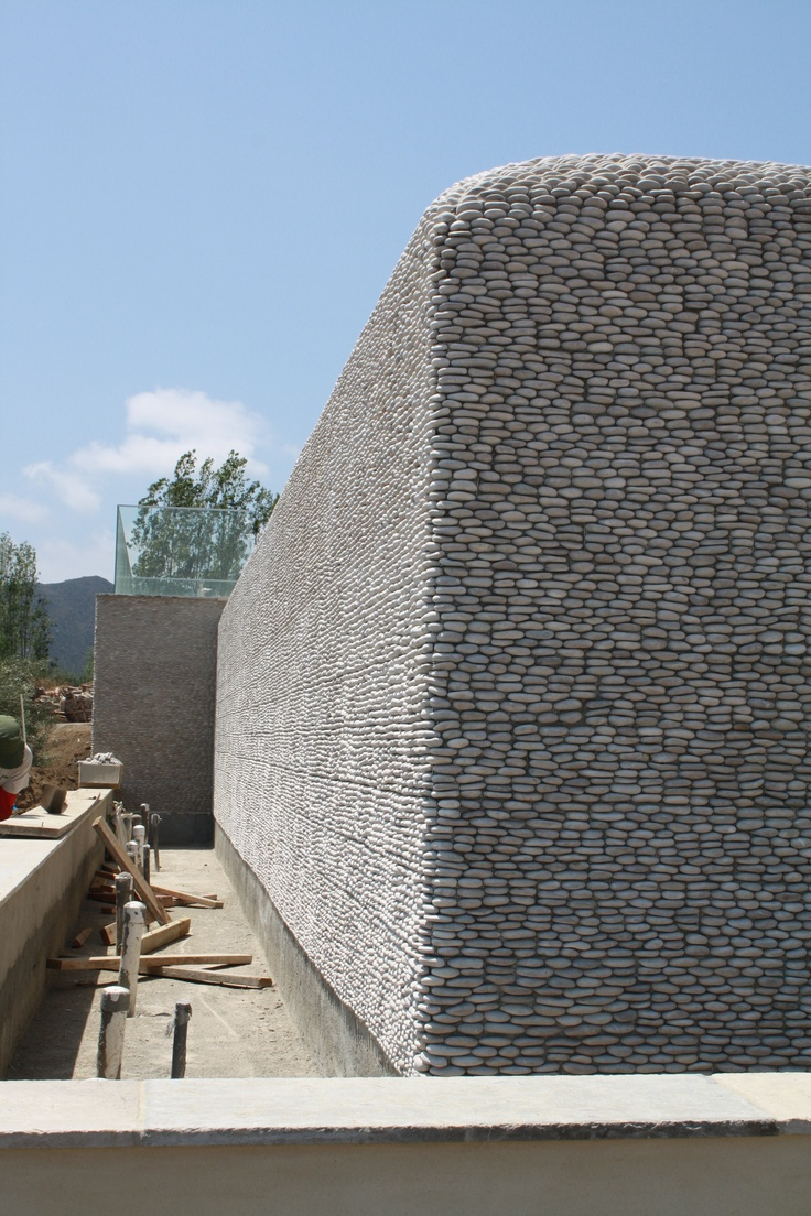 Tan standing pebbles wall fountain in construction.  Pebble tiles by zen paradise inc.