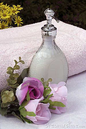 Liquid soap a pink towel and silk flowers