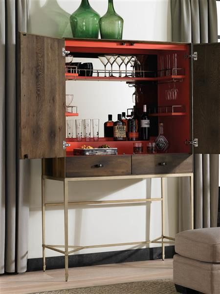 Product Name: Miters Touch by Caracole Lofty intentions. Make good on your intentions to entertain at home from a cool cocktail bar hidden away in this handsome cluster fumed oak cabinet. Resting on its high perch of artisan metal, a retro-modern cocktail bar awaits and offers an unexpected blast of color. The bar's interior is clad in blood orange and fitted with shelves to hold cocktail glasses.. Available exclusively at Space Design Collective in India. www.spacedesigncollective.com
