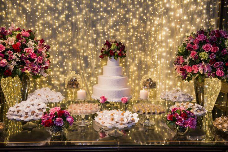 Mesa do bolo com painel de luzes, bolo, docinhos, macaroons, flores e velas