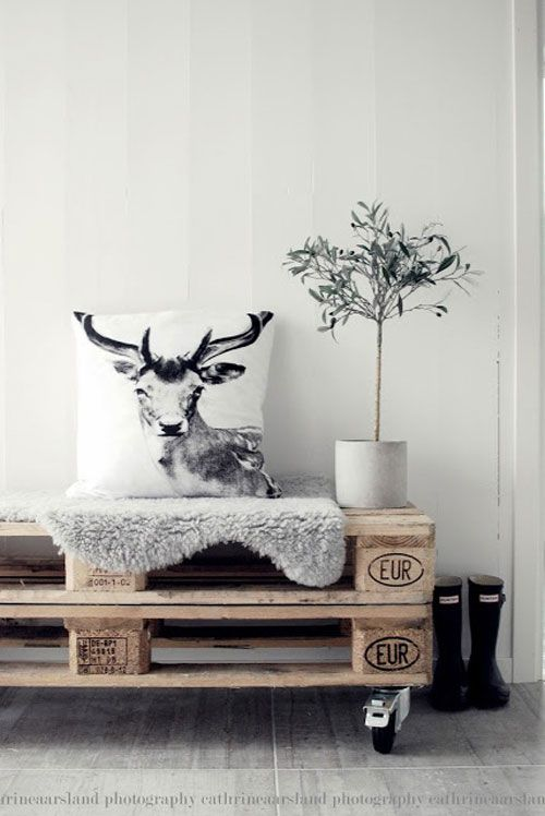 home decor display - pallet table with exotic throw pillow and white walls.