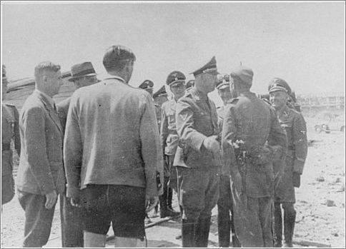 During a tour of the Monowitz-Buna building site, Reichsfuehrer SS Heinrich Himmler speaks to a member of the SS who is supervising the prisoners working on the construction of the IG Farben plant