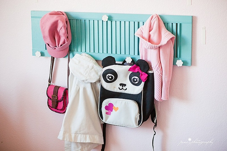 An old shutter and some inexpensive knobs makes a great coat and backpack hanger.