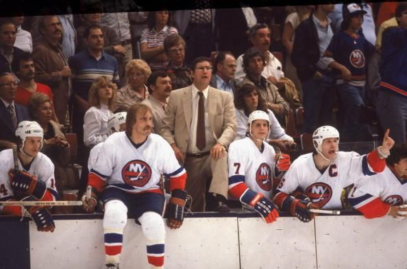 Al Arbour Surrounded By A Wall Of White Jerseys In 1982:  #14 Bob Bourne, #23 Bob Nystrom, #7 Stefan Persson, #5 Captain Denis Potvin and #1 Roland Melanson.