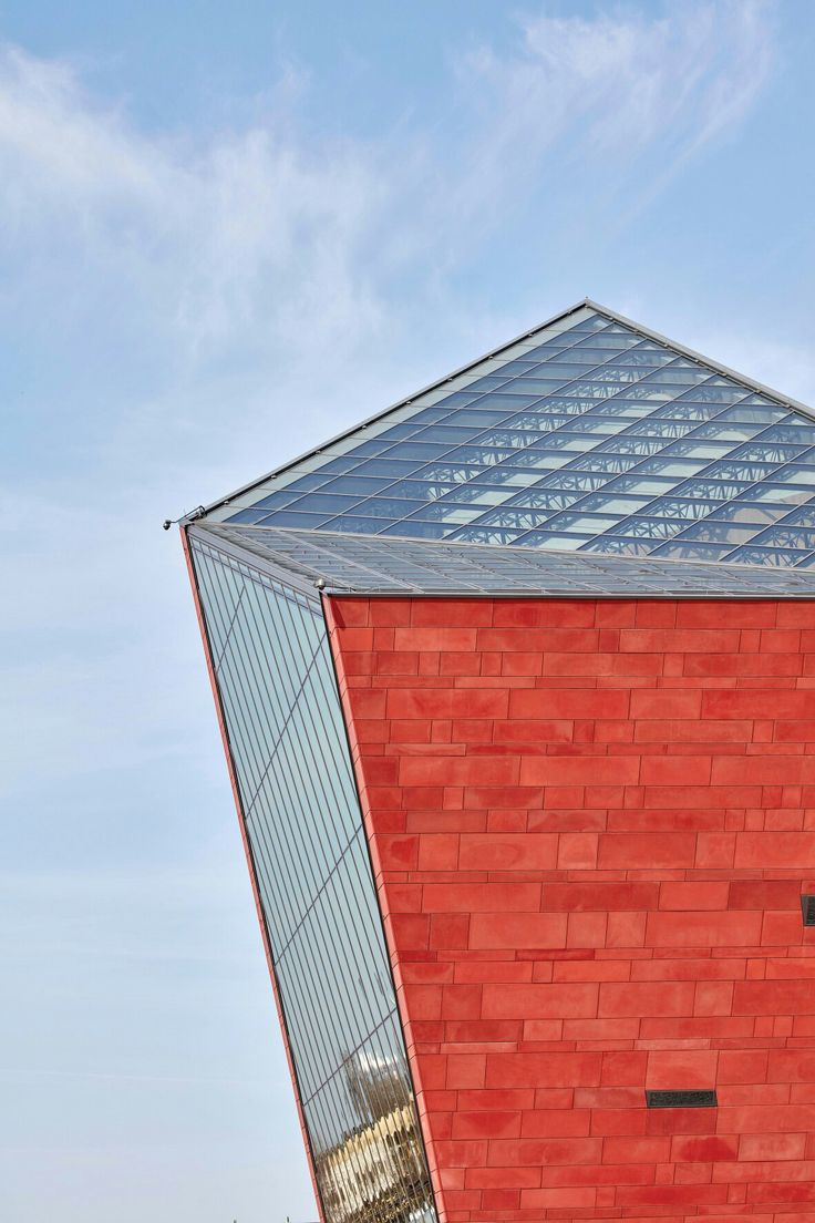 Tilted red tower marks entrance to Polish war museum by Kwadrat