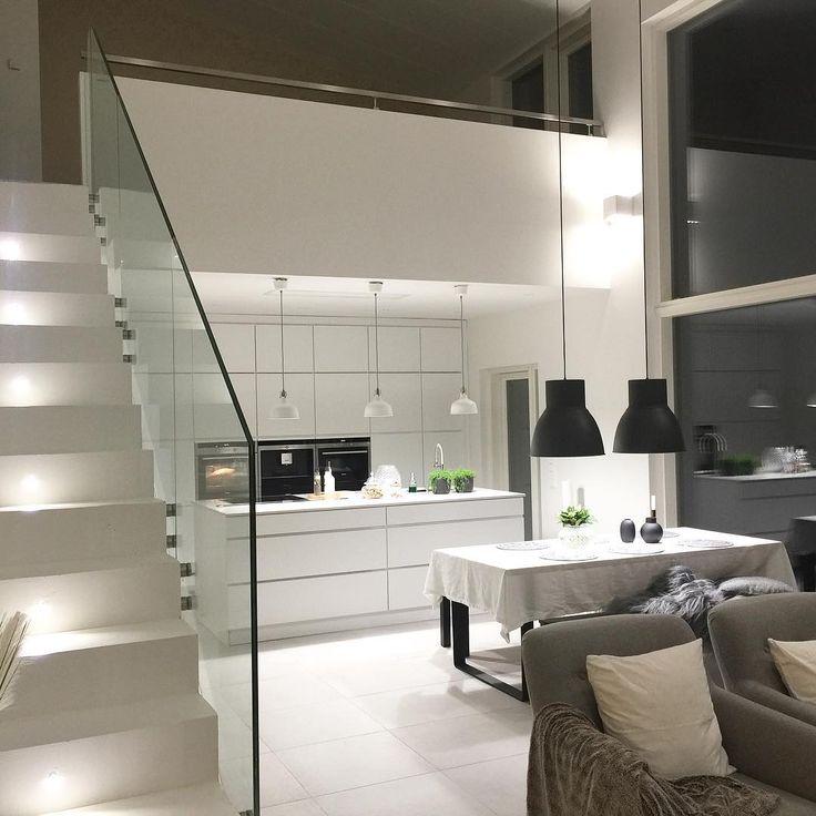 Moderni valkoinen keittiö, korkea tila ja näyttävä lasikaide tuovat sisustukseen ylellistä tunnelmaa.