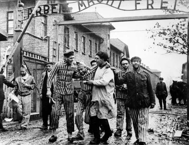 "Survivors of the Auschwitz concentration camp are helped by Russian medic past the main gate with the infamous sign reading  Arbeit Macht Frei which means ""Work liberates."" The concentration camp was liberated on 27 January 1945 by the 100th Infantry Division of General F.M. Krasavina (1st Ukrainian Front)."