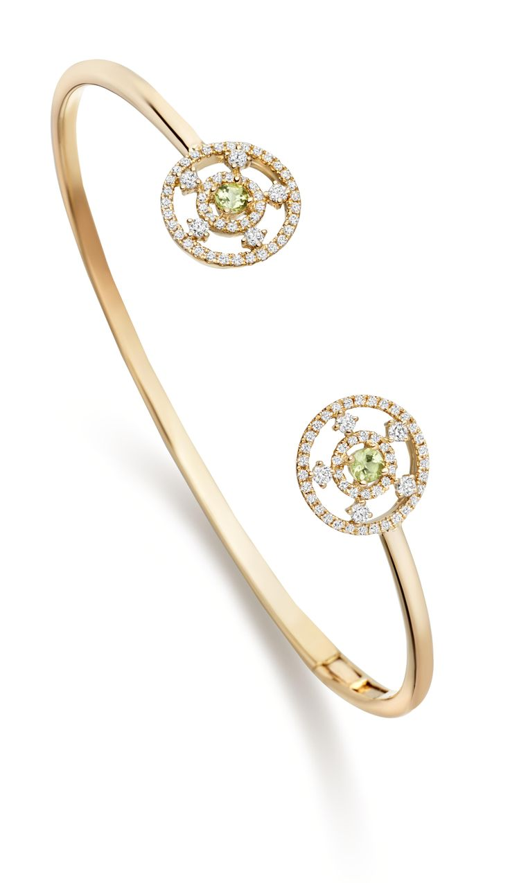 An exquisite yellow gold bangle set with two intricate diamond circles encasing green amethyst stones the hinge design makes it incredibly easy to put on