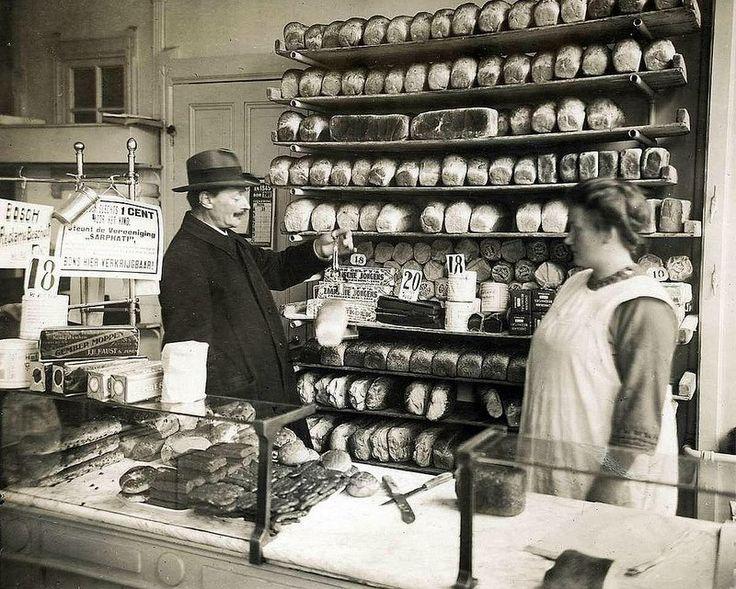 1926 Keuringsdienst van waren in bakkerij  Een ambtenaar van de Keuringsdienst van Waren keurt een brood door het te wegen met een handweegschaaltje. Hij staat achter de toonbank in de winkel van de bakker, naast de verkoopster. In de schappen achter hen liggen rijen broden . Op de toonbank liggen verschillende koeken