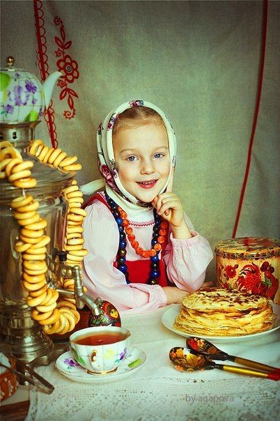 A smiling Russian girl in a traditional costume is sitting at the tea-table with pancakes, samovar and nice dishes.