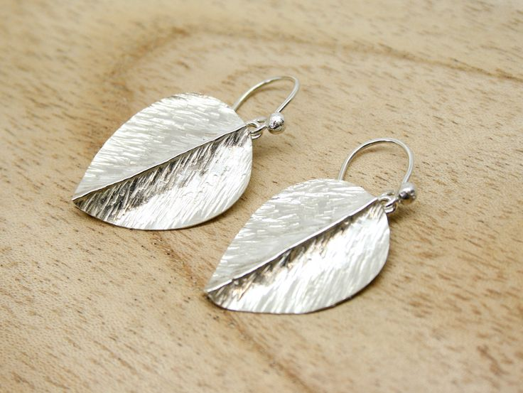 A delightful pair of handmade silver leaf earrings. Created from sheet silver the leaves are fold formed and lightly hammered to create this beautiful effect. The leaves articulate from their silver hook fittings and have a total length of 38mm. Each leaf measures 19mm x 25mm.  #earrings #leaf #silver #jewellery #cornwall #uk #gb #westcountry #devon #england #silversmith #pretty #jeweller #jewellers #handmadejewellery