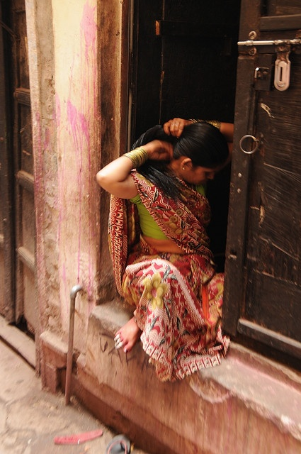 indian lady doing her hair in the doorway of her house