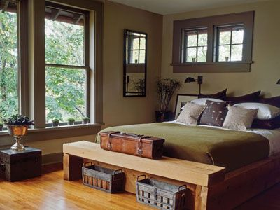 "Moody Green    ""Draw inspiration from the earth tones outside,"" says Eddie Ross, editorial director of Rue La La Living. ""The green color of moss, the deep blues and grays in the sky—these are the colors that feel naturally cozy this time of year."" In this bedroom, a wall painted sage sets a neutral backdrop, while brown trim and rich furnishings complete the rustic palette."