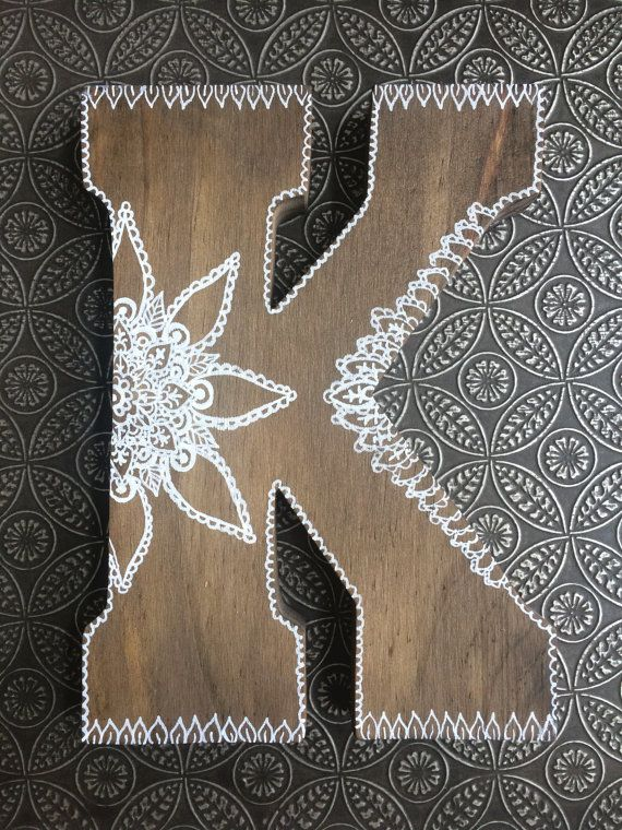 This wooden letter has a light stain and is hand decorated with white paint. Each design is inspired by henna tattoo artwork, and each letter is