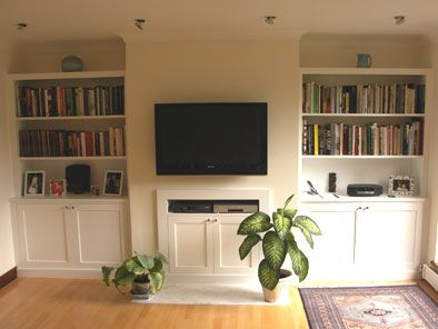 Alcove shelves and cupboards set back on either side of TV wall; wall opposite bed wall