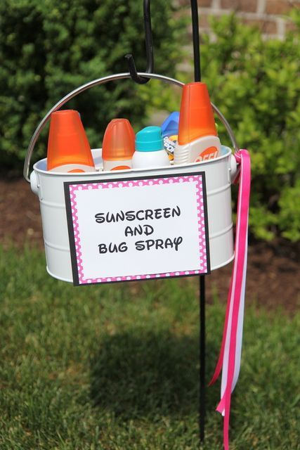 Sunscreen and bugs spray in a bucket on a shepherd's hook.