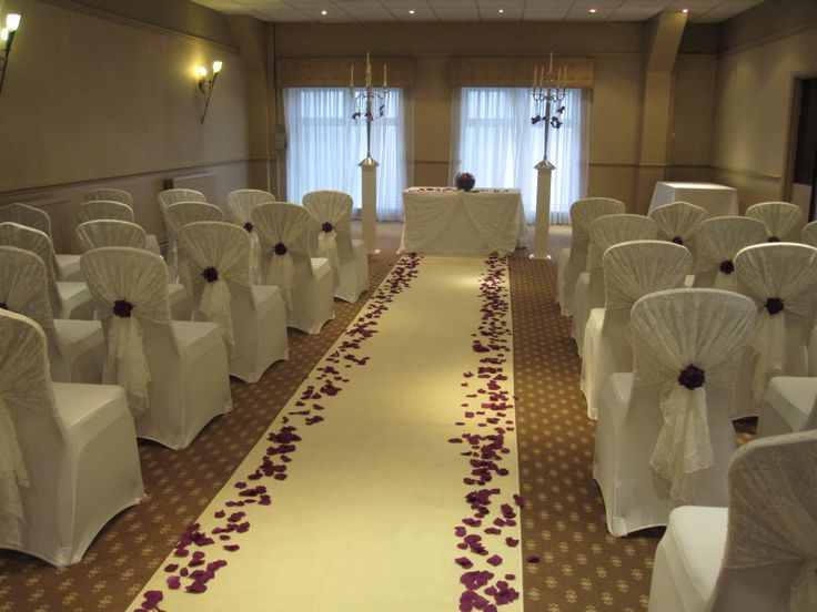 Delicate white lace hoods finished with a purple silk rose, complimented by Couture Chair Covers & Venue Dressings ivory aisle carpet scattered with purple silk petals.
