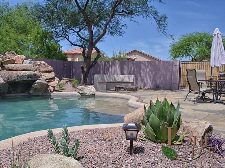 This landscape features a fire pit barbecue flagstone for Garden pool in arizona